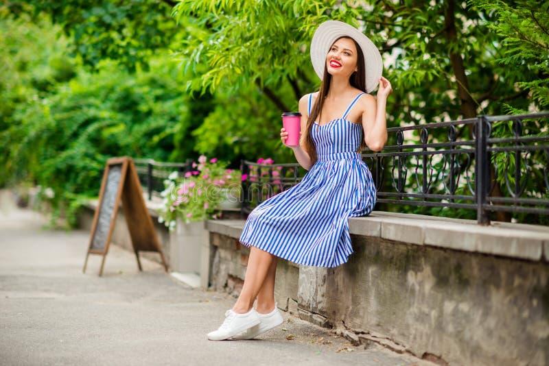 Fotoet av att förbluffa damen som dricker smakligt kaffe Togo som ser himmel i tystnad, parkerar upp till klädersolhatten och den royaltyfri foto