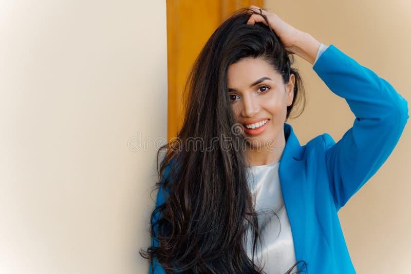 Fotoet av bra se brunettdamen med försiktigt leende, mörkt hår, iklädd elegant formell dräkt, har fylliga kanter, sund hud, arkivfoton
