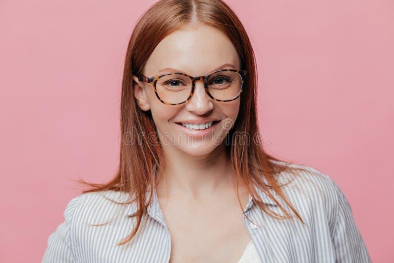 Fotoet av den attraktiva gladlynta unga kvinnan med glat tillfredsställt uttryck, brunt hår, ler i huvudsak, bär anblickar som gl arkivbild