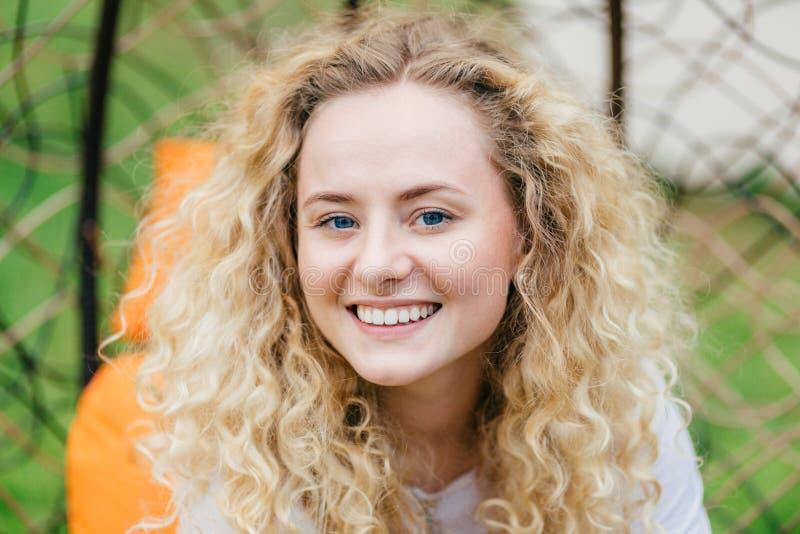 Fotoet av den attraktiva lockiga blonda kvinnlign med glänsande leende, vita även tänder för shower och att vara i hög ande, tyck royaltyfri bild