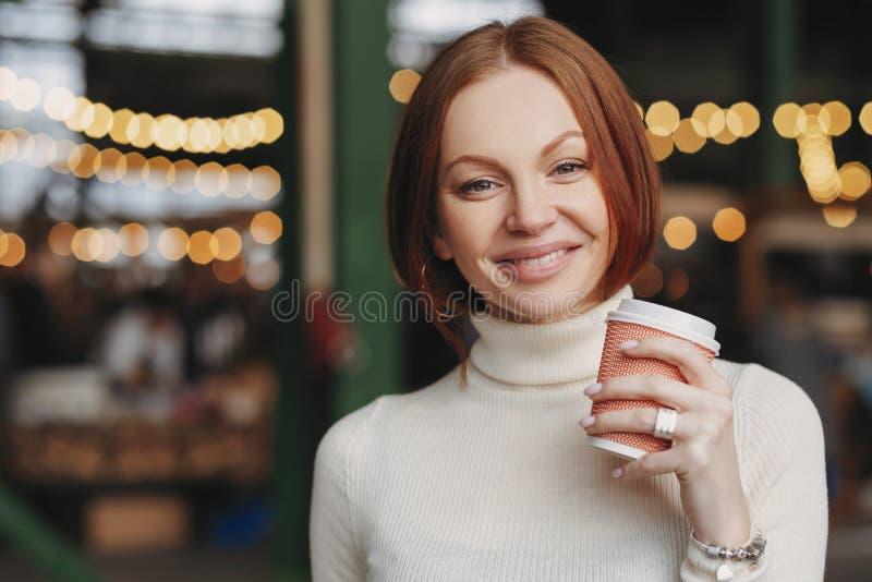 Fotoet av den attraktiva unga kvinnan rymmer takeaway kaffe, har behagit uttryckt, det toothy leendet, iklätt vitt förkläde, pose royaltyfri bild