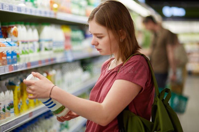 Fotoet av den attraktiva unga kvinnliga konsumentmodellen med den guppade frisyren, den iklädda tillfälliga t-skjortan, ställning arkivfoton