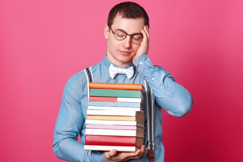 Fotoet av den exuasted stiliga studenten som rymmer den enorma bunten av böcker, lider från den ruskiga huvudvärken, den iklädda  royaltyfria bilder