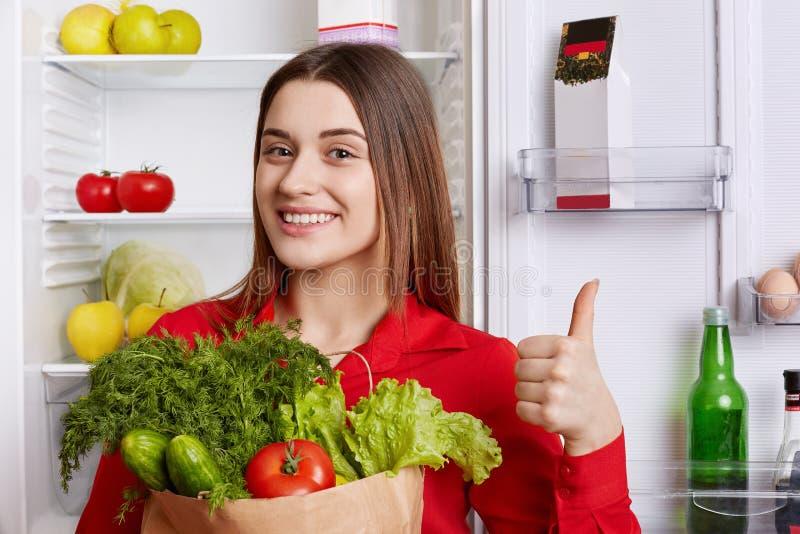 Fotoet av den glade kvinnlign visar det ok tecknet och visar godkännande, rymmer grönsaker, kommer från specerihandlare som ` s s royaltyfria foton