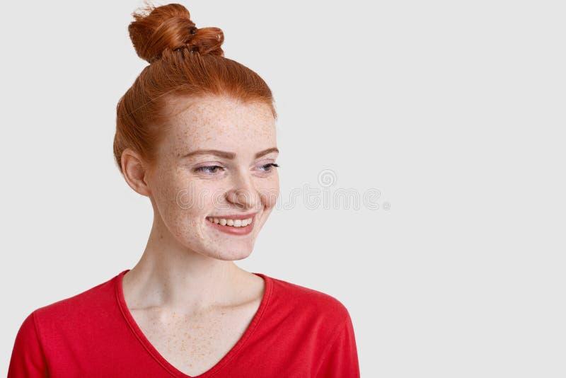 Fotoet av den glade tonårs- flickan med tillfredsställt uttryck som åt sidan fokuseras, har positiv framtidsutsikt, tänker om någ royaltyfria foton