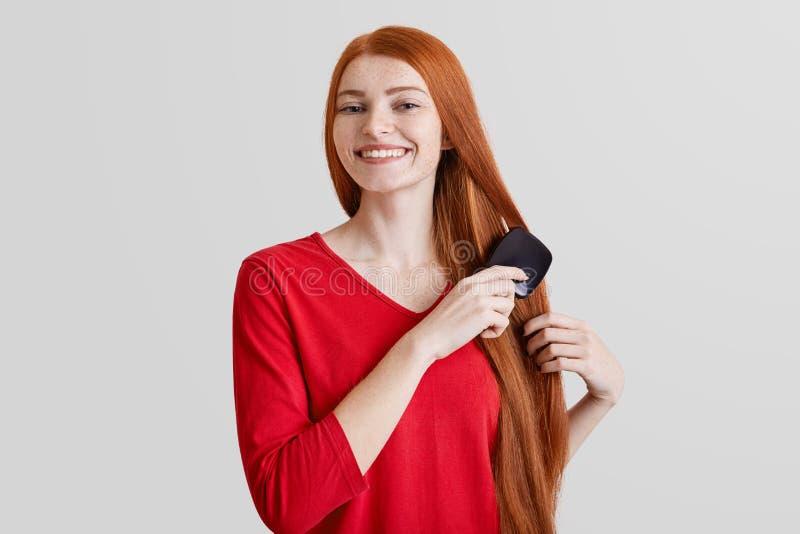 Fotoet av den gladlynta le fräkniga ljust rödbrun unga kvinnan kammar hennes långa röda hår som är glat att förbereda sig för dat royaltyfri bild