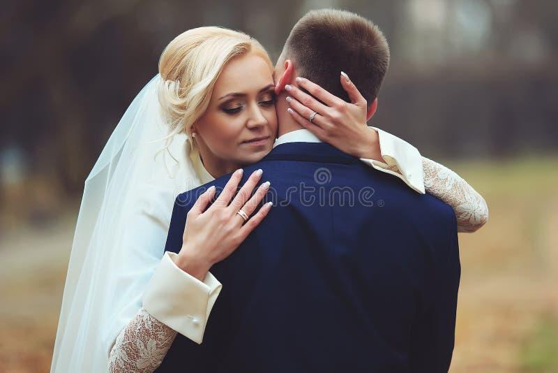 Fotoet av den härliga bruden som omfamnar brudgummen från baksida på, parkerar arkivfoton