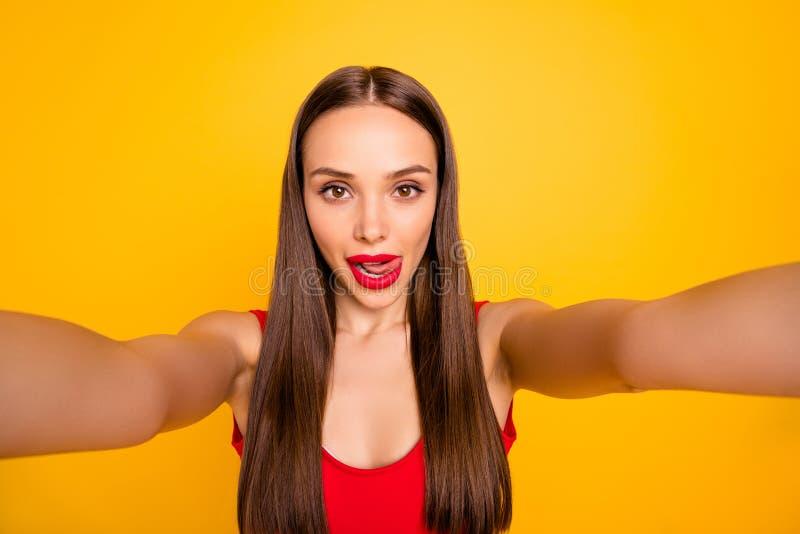 Fotoet av den härliga fantastiska älskvärda damen som gör selfiesaningkanten kokedda kläder den röda baddräkten, isolerade gult royaltyfria foton