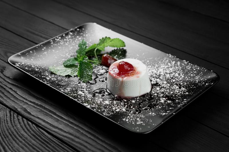 Fotoet av den italienska pannacottaefterrätten med jordgubbesirap och mintkaramellen spricker ut på den svarta träbakgrunden royaltyfri foto