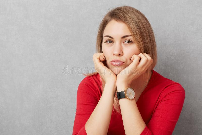 Fotoet av den ledsna nätta kvinnan lutar på händer, trutar kanter, bär den trendiga klockan, och den röda tröjan, ser med upprive royaltyfri foto