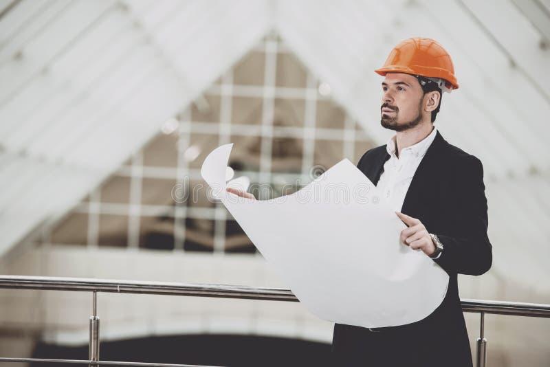 Fotoet av den manliga arkitekten i rött hardhatinnehav gör en skiss av royaltyfri fotografi