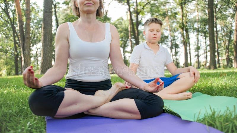 Fotoet av den mellersta ?ldriga modern med hennes barn f?r den ton?rs- pojken som g?r yoga och andas ?vningar p?, parkerar Familj arkivbild