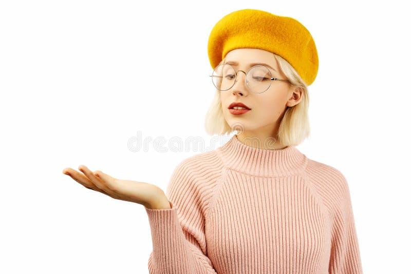 Fotoet av den stiliga positiva flickan, uppehällen gömma i handflatan lyftt mot den vita tomma väggen, visar något som är angenäm royaltyfria bilder