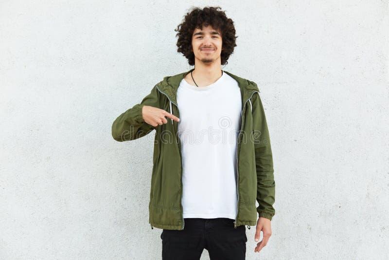 Fotoet av den tillfredsställda le hipsteren har skägget, lockigt hår, indikerar med pekfingret på kopieringsutrymme av hans kläde arkivbilder