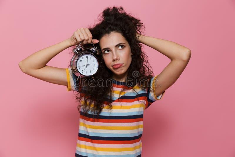 Fotoet av den upprivna kvinna20-tal med innehavringklockan för lockigt hår, är royaltyfria foton
