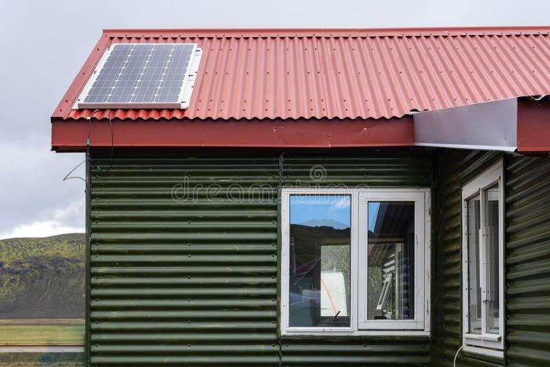 Fotoet av det gröna lilla komforthuset med röda nitar tak och solpanel installerar överst mot fridsam blå himmel arkivfoto