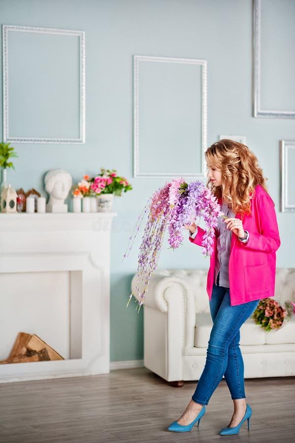 Fotoet av en härlig flicka i ett rosa omslag och jeans dekorerade på våren inre av huset fotografering för bildbyråer