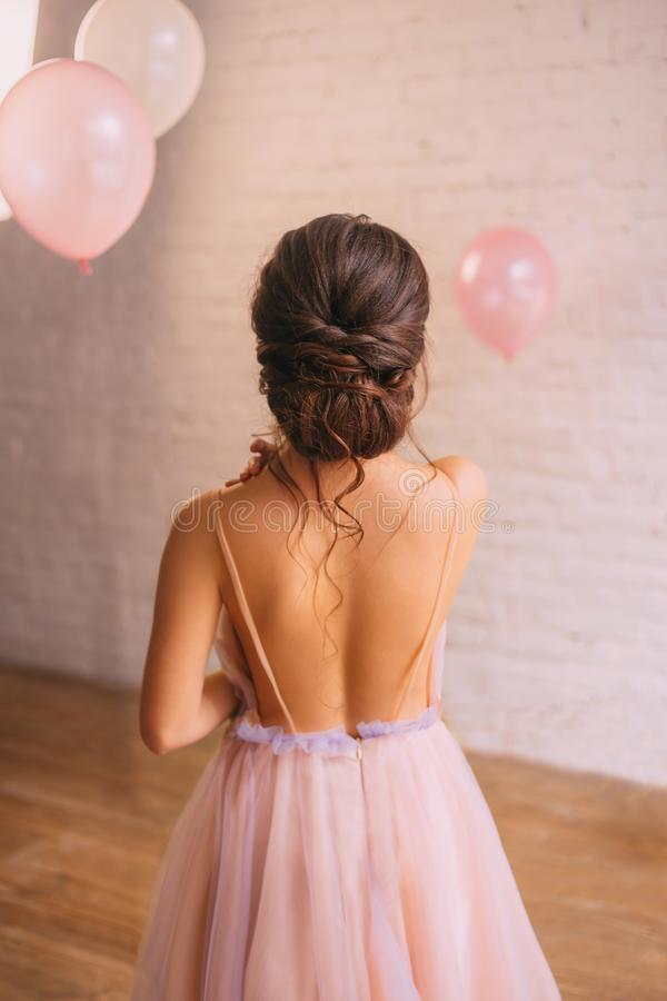 Fotoet av en ung attraktiv jungfru med att förbluffa hud bakom, flickan är iklätt en ljus delikat persikaklänning med arkivfoton
