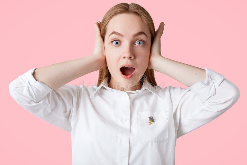 Fotoet av förargade kvinnliga proppar gå i ax som hör hög musik, har det chockade uttryckt, blåa ögon, och mjuk sund hud, bär blo fotografering för bildbyråer