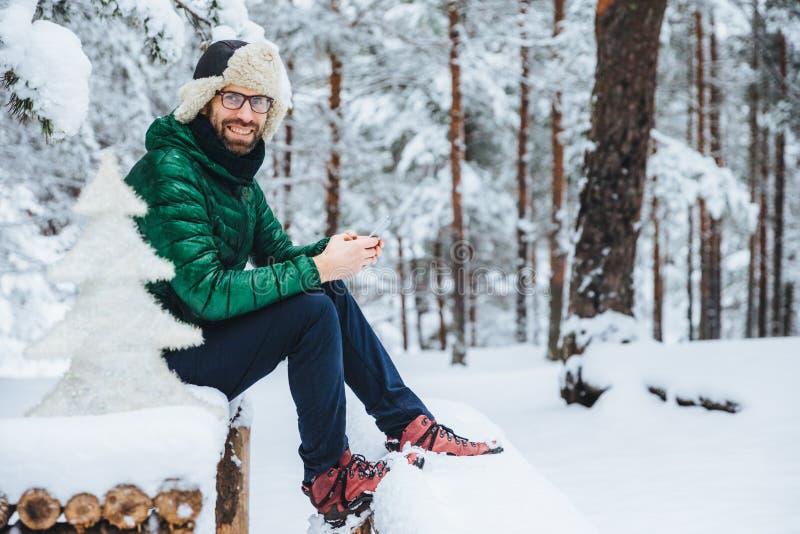Fotoet av gladlynta manliga typmeddelanden på den smarta telefonen ser direkt in i kamera, sitter i den vita vinterskogen, ler ly royaltyfri foto