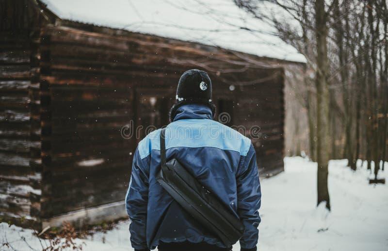 Fotoet av lycksökarefotvandraren i snö täckte skogen framme av den övergav stugasikten från hans baksida Fotvandrareman i blått o royaltyfri fotografi