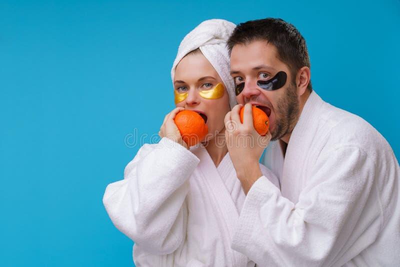 Fotoet av mannen och kvinnan med stelnar block under ?gon och i den vita ?mbetsdr?kten som biter apelsiner fotografering för bildbyråer