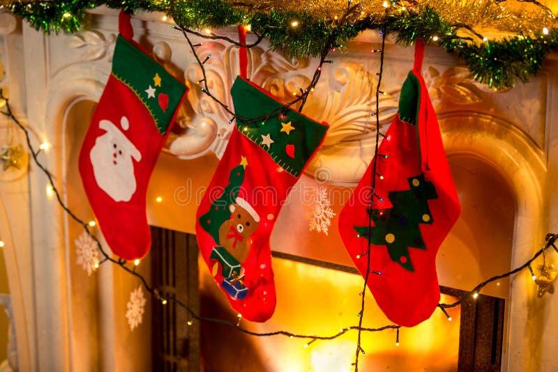 Fotoet av tre röda jul slår att hänga på den brinnande spisen arkivbilder