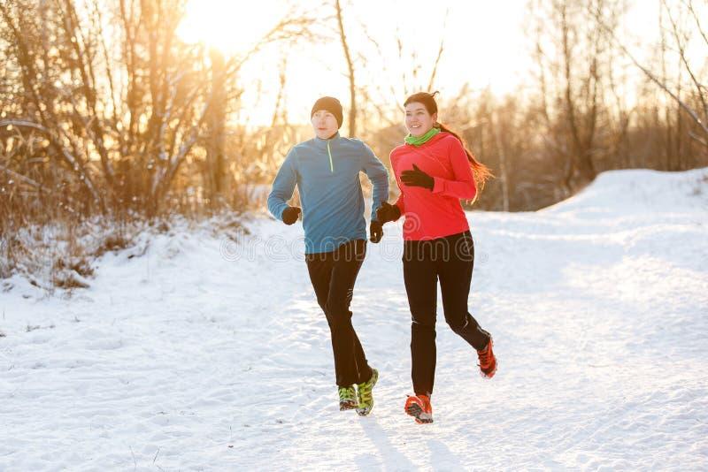Fotoet av två idrottsman nen på inkörd vinter för morgon parkerar arkivbilder