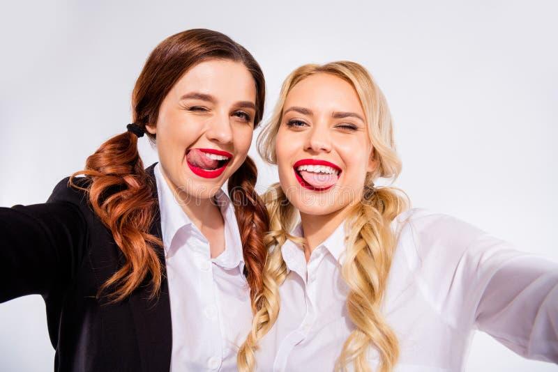 Fotoet av två klasskompisdamer som gör selfies som blinkar ögon, bär skjortor vit bakgrund royaltyfria bilder