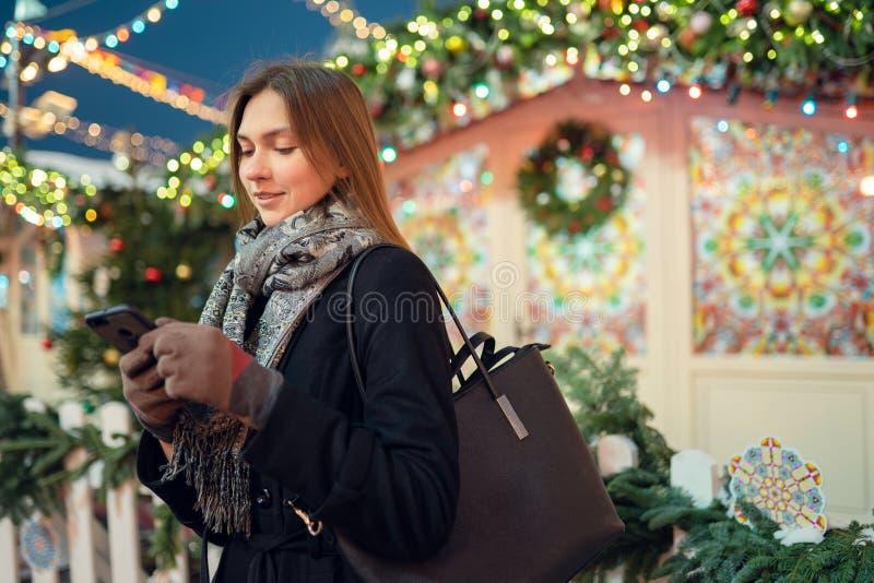 Fotoet av unga flickan med telefonen i händer på vinter går i stad royaltyfri fotografi
