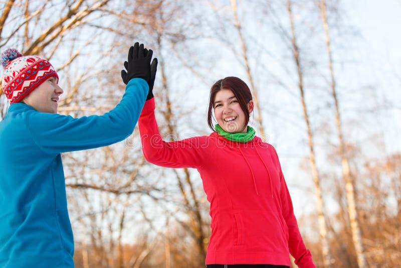 Fotoet av unga idrottsmän som gör handskakningen i vinter, parkerar på eftermiddagen royaltyfria foton