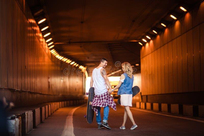 Fotoet av unga kvinnlig- och manpar håller händer tillsammans, bär skateboarder som är involverade i aktiv livsstil, går across fotografering för bildbyråer