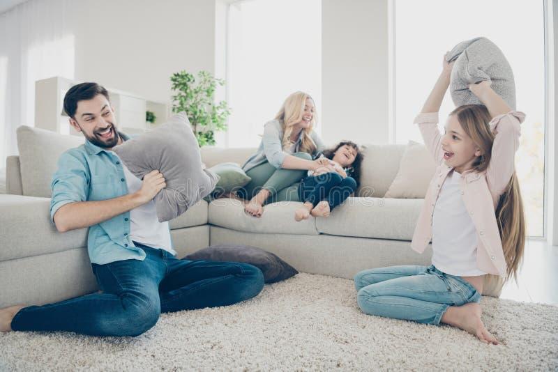 Fotoet av vårdar familj, fyra som medlemmar spenderar fritid som jublar fniss för kuddekamp, sitter soffavardagsrum arkivfoto