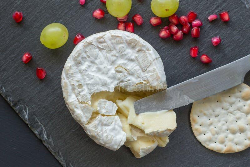 Fotoet för sikten för camembertostöverkanten på kritiserar ostbrädet arkivbilder