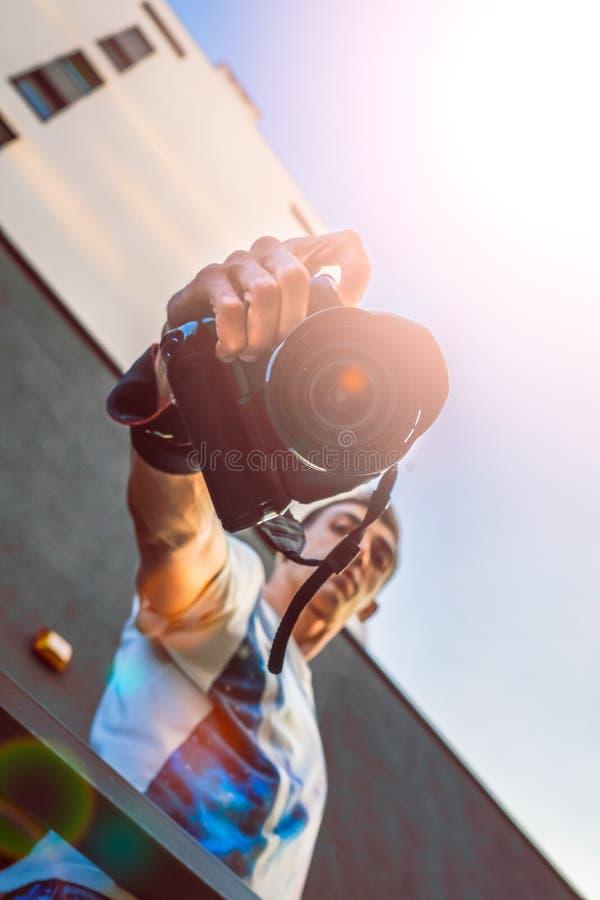 Fotoet för solsignalljussolnedgången av det manliga turist- eller fotografdanandefotoet på parallell kamera för tappninghipsterfi arkivbilder