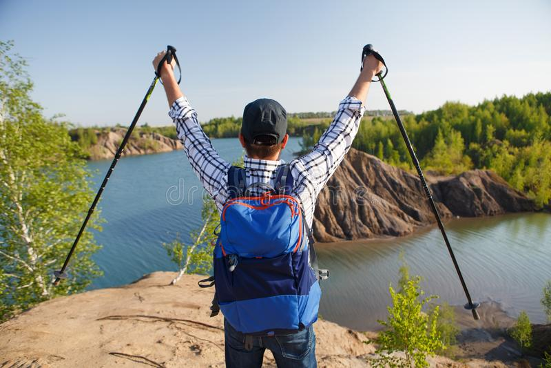 Fotoet från baksida av den turist- mannen med att gå klibbar med hans händer upp på bergkullen nära sjön royaltyfri foto