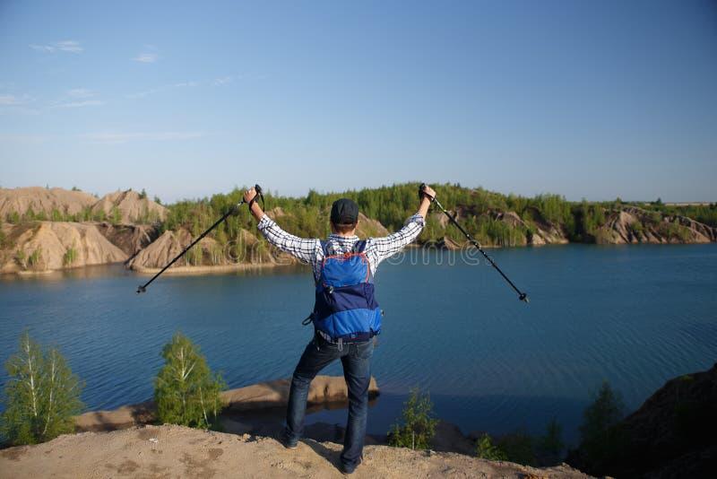Fotoet från baksida av den unga turisten med ryggsäcken med armar lyftte med att gå pinnar på bakgrund av berglandskapet fotografering för bildbyråer