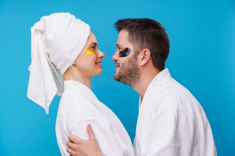 Fotoet på sida av mannen och kvinnan med stelnar block under ögon och i den vita ämbetsdräkten arkivbilder