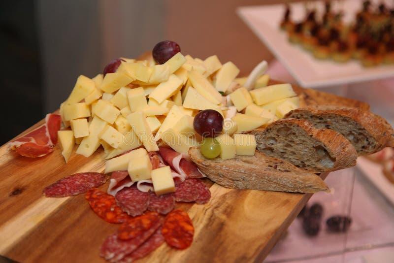 Fotoet skivade och ordnar till för att äta variation av foods: olika sorter av ost, kurerad skinka, den rökte korven, druvor och  royaltyfri bild