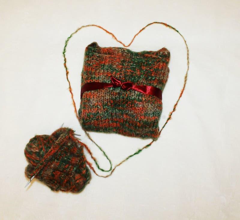 Fotofarbe, warmes, gestricktes Geschenk gebunden mit einem Bogen mit einem Strang des Threads auf einem weißen Hintergrund lizenzfreie stockbilder