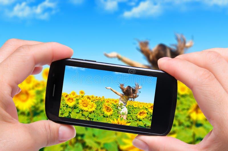 Fotoflicka i ett fält av solrosor fotografering för bildbyråer