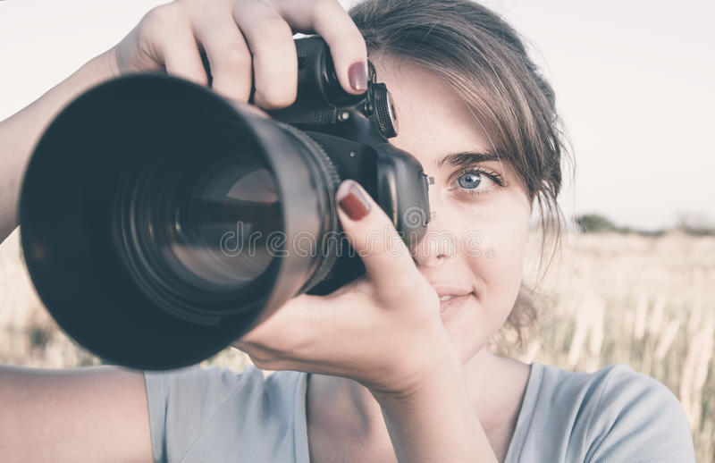 Fotoframsida av en ung kvinna med fotografisk utrustning i fältet som arbetar för hennes nöje royaltyfri fotografi
