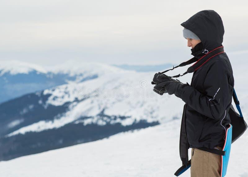Fotograaf in de winter, bovenop de berg stock afbeelding