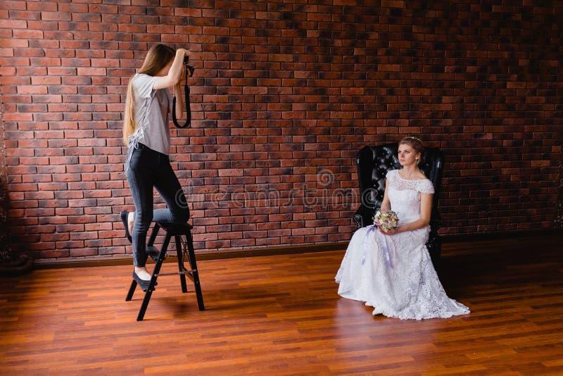 Fotograaf die beelden nemen de bruid in de studio op een grote leerleunstoel stock foto's