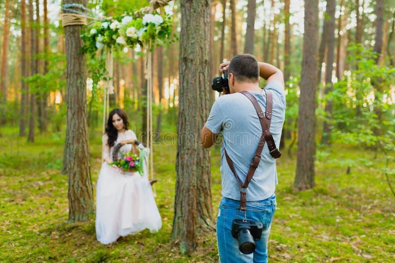 Fotograaf die beelden van de bruid op een kabelschommeling nemen royalty-vrije stock foto's