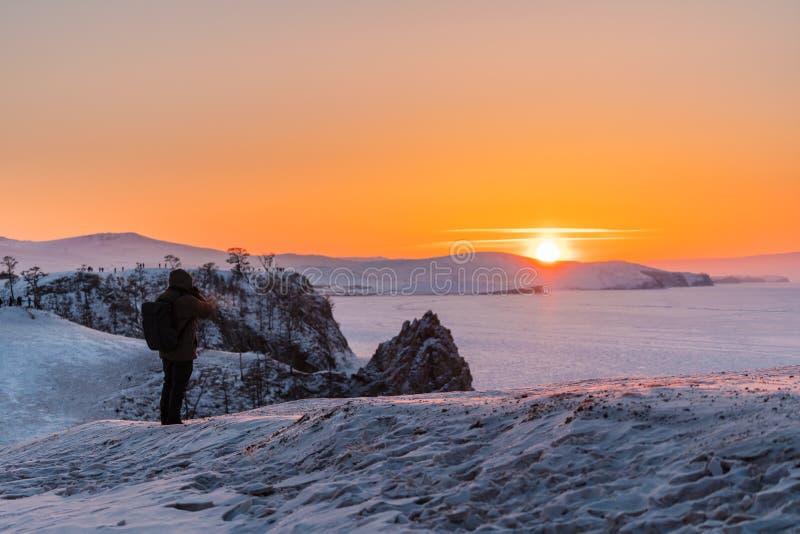 Fotograaf die foto van zonsonderganglandschap nemen in de winter bij meer Baikal, Rusland stock foto's