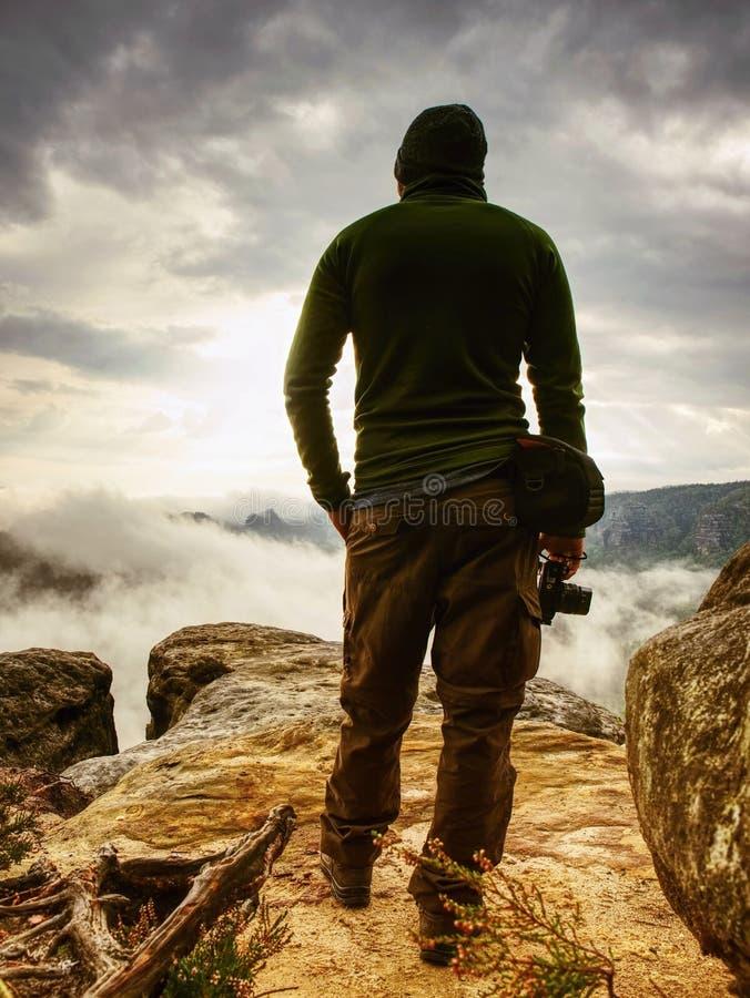 Fotograaf die op bergklip mistwandelaar de onderzoeken zal beeld nemen royalty-vrije stock foto