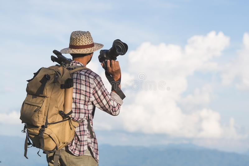 Fotograaf die zijn camera houden De reizigers houden een DSLR-camera op de berg stock foto
