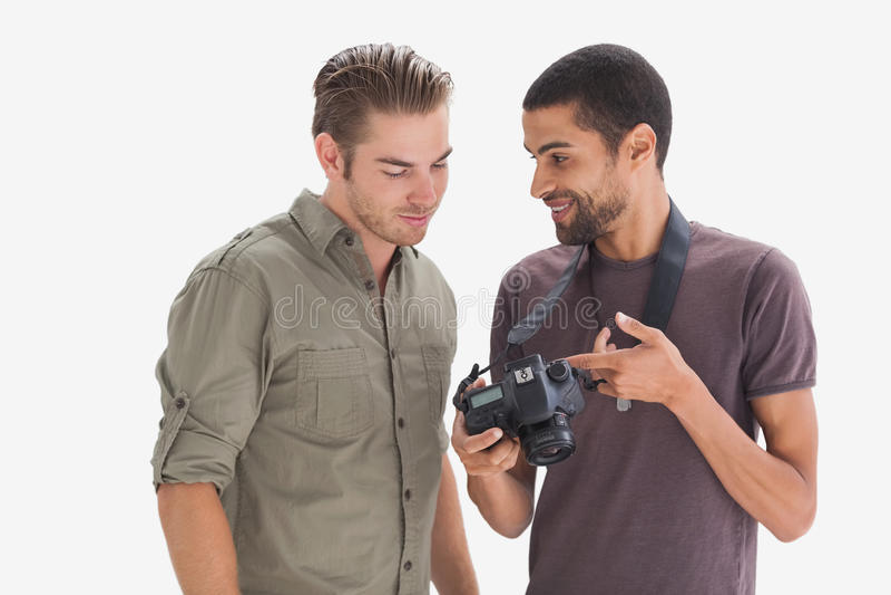 Fotograaf die zijn vriendenfoto op camera tonen stock foto's