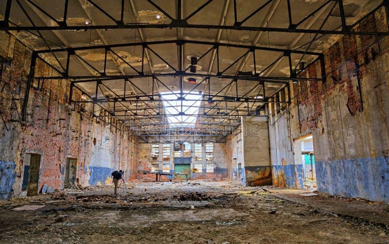 Fotograaf in een oude verlaten fabriek royalty-vrije stock afbeeldingen